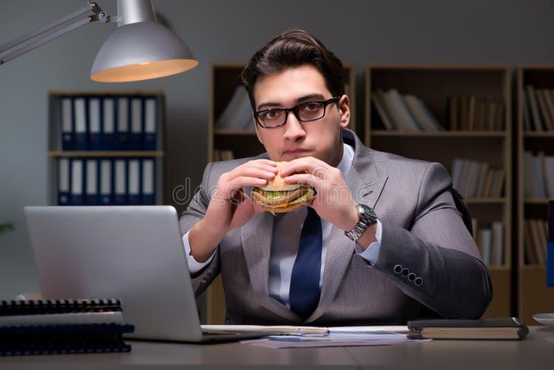 L'homme d'affaires tard la nuit mangeant un hamburger image stock