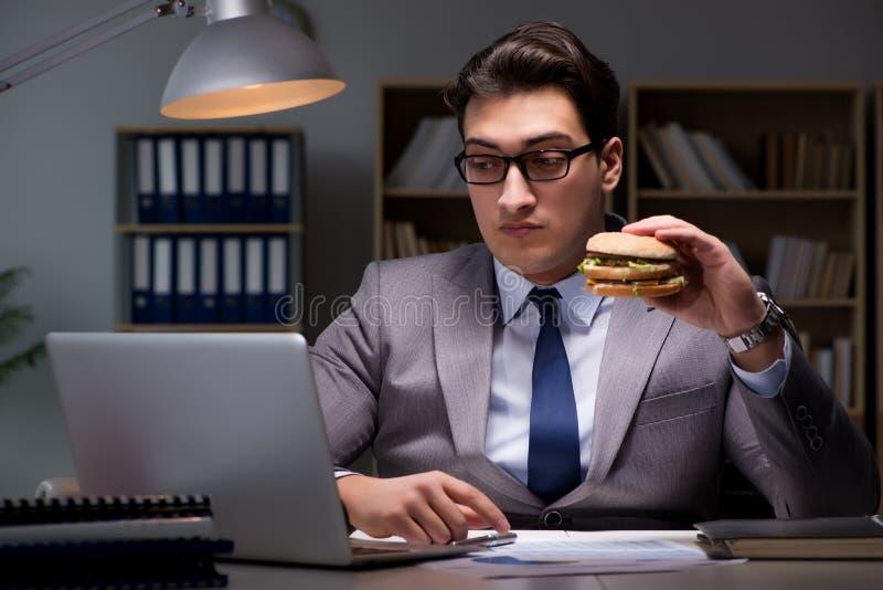 L'homme d'affaires tard la nuit mangeant un hamburger images libres de droits