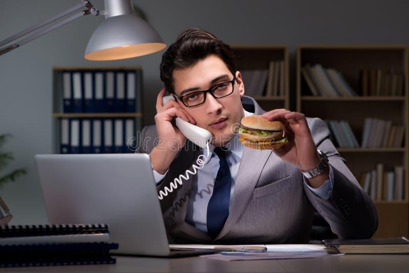 L'homme d'affaires tard la nuit mangeant un hamburger photos stock