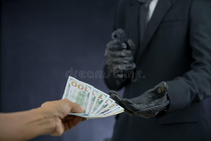 L'homme d'affaires tenant des armes à feu a pillé l'argent de quelqu'un images stock