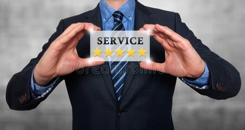 L'homme d'affaires tenant la carte blanche avec des étoiles du service cinq signent, Gre images stock