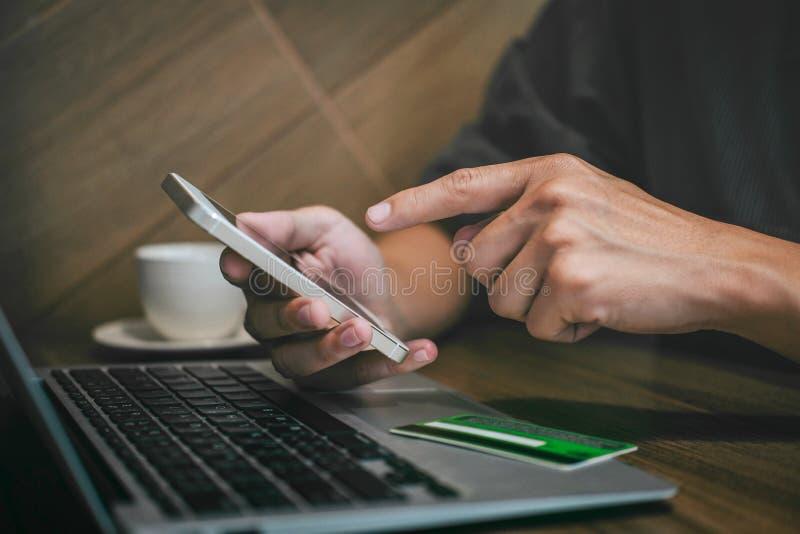 L'homme d'affaires tenant la carte de crédit et à l'aide du smartphone sur l'ordinateur portable pour des achats et le paiement e photos stock