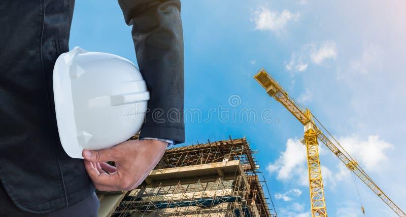 L'homme d'affaires tenant la sécurité blanche de casque au chantier de construction avec le fond de grue photo stock