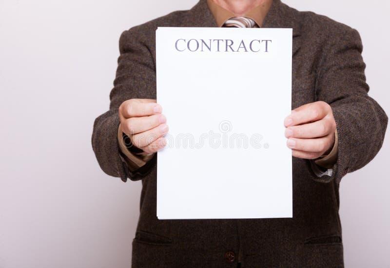 L'homme d'affaires tenant le papier blanc avec signent le contrat photos stock