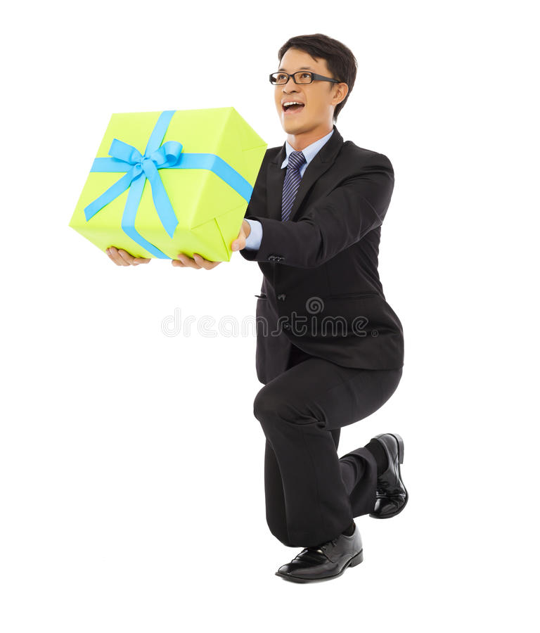 L'homme d'affaires tenant un boîte-cadeau et se mettent à genoux vers le bas photos libres de droits