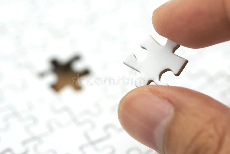 L'homme d'affaires tenant un puzzle blanc est placé sur un puzzle blanc utilisation en tant que le concept d'affaires de fond et  photo stock