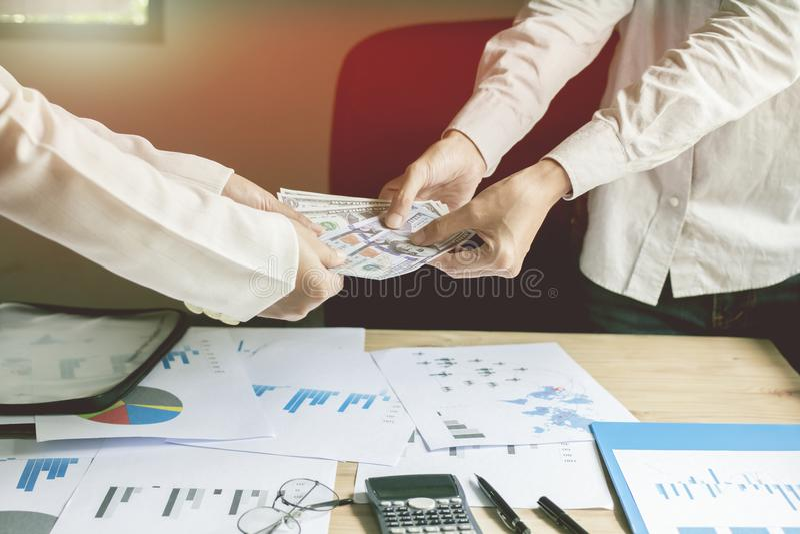 L'homme d'affaires tient la banque avec l'équipe et les papiers sur mon bureau allument le fond de coucher du soleil images libres de droits