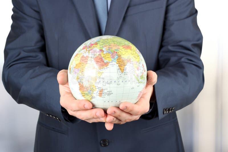 L'homme d'affaires tient le globe dans une main image stock