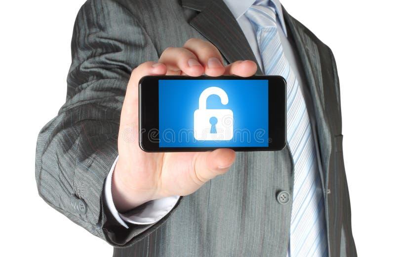 L'homme d'affaires tient le téléphone intelligent avec la serrure image libre de droits
