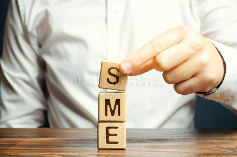 L'homme d'affaires tient les blocs en bois avec le mot PME Petites et moyennes entreprises - entreprises commerciales qui ne dépa photos libres de droits