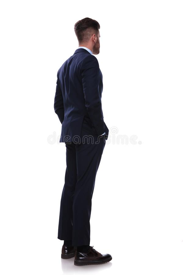 L'homme d'affaires tourné dans le costume de marine regarde pour dégrossir photos stock