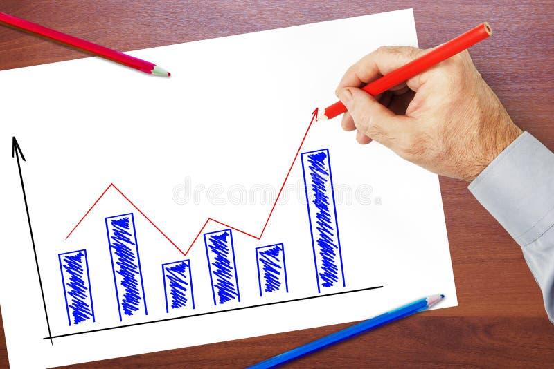 L'homme d'affaires trace un graphique d'augmentation et de croissance photo libre de droits