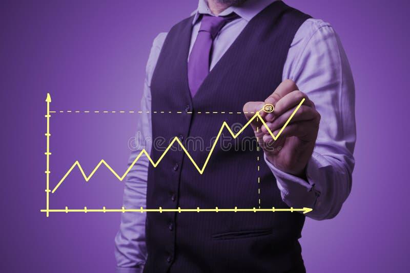 L'homme d'affaires trace un graphique de croissance photo stock