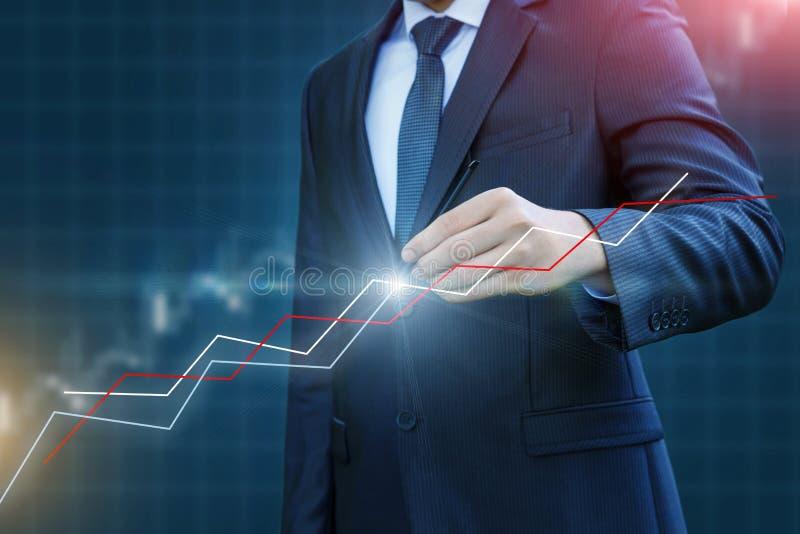 L'homme d'affaires trace un graphique de la dynamique image stock