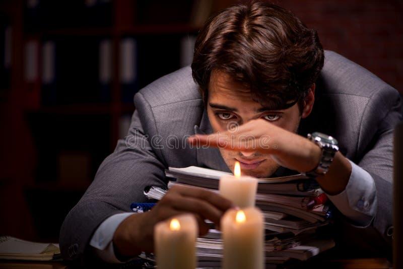 L'homme d'affaires travaillant tard dans le bureau avec la lumi?re de bougie photo libre de droits