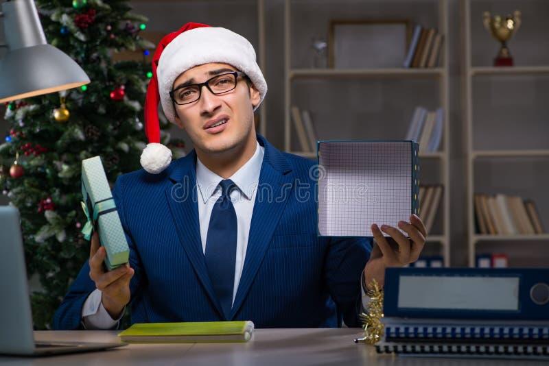 L'homme d'affaires travaillant tard sur le jour de Noël dans le bureau photos stock