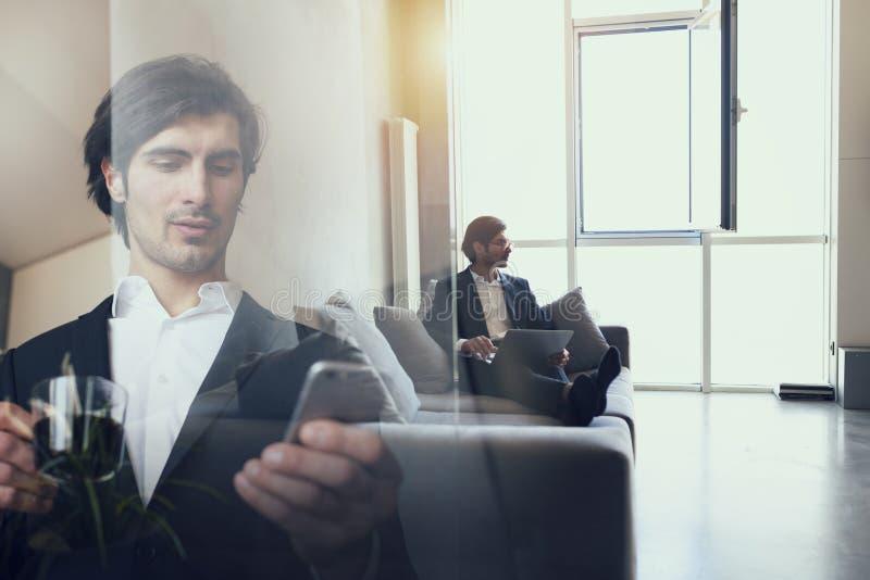 L'homme d'affaires travaille avec son smartphone dans le bureau Double exposition images libres de droits