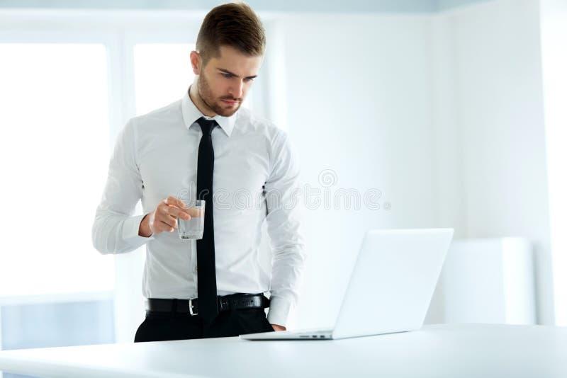 L'homme d'affaires travaille sur son ordinateur au bureau photographie stock