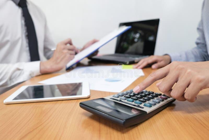 L'homme d'affaires utilise une calculatrice pour calculer les nombres images libres de droits