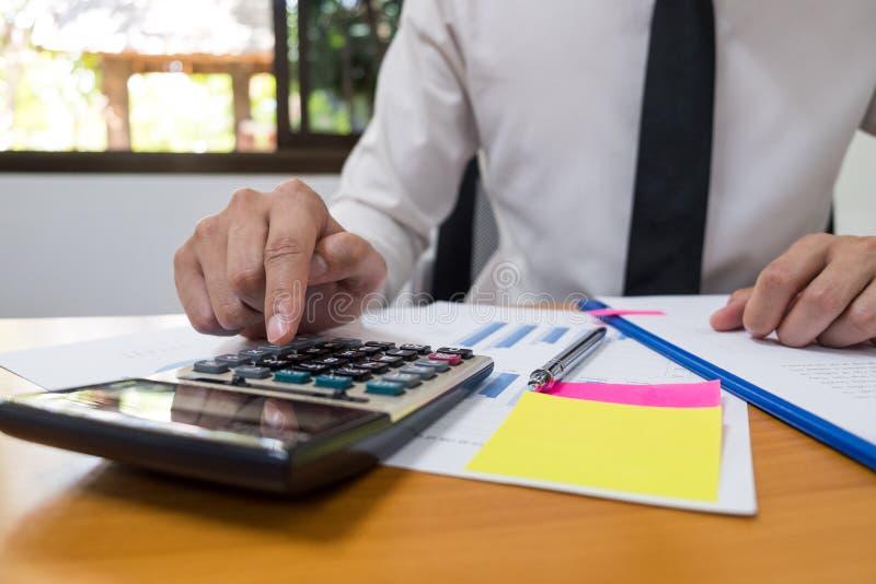 L'homme d'affaires utilise une calculatrice pour calculer les nombres image libre de droits