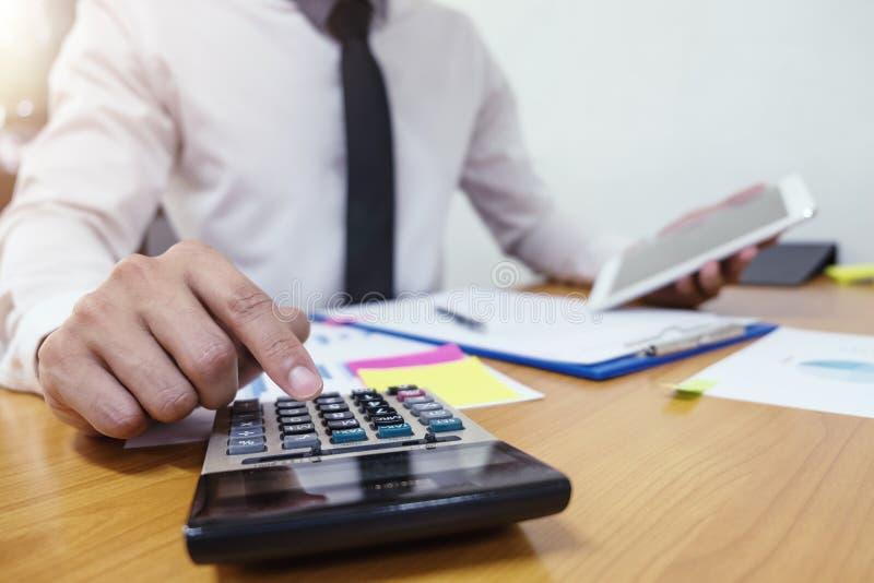 L'homme d'affaires utilise une calculatrice pour calculer les nombres photographie stock libre de droits
