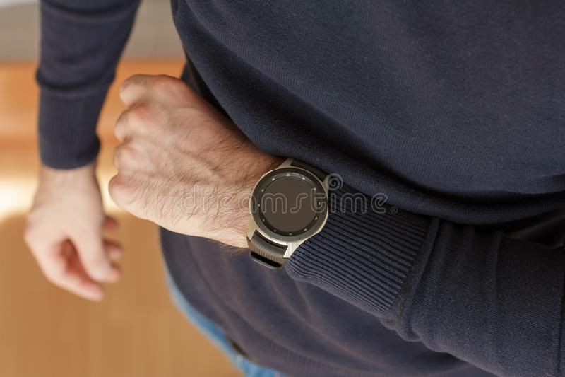 L'homme d'affaires utilise une montre intelligente sur son intérieur de main du bureau Fermez-vous vers le haut du regard photos libres de droits