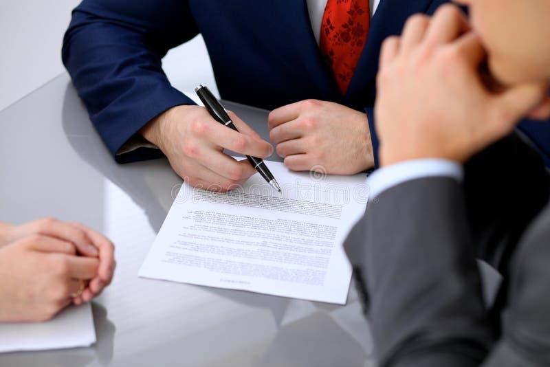 L'homme d'affaires va signer le contrat Groupe de gens d'affaires lors du contact photos libres de droits