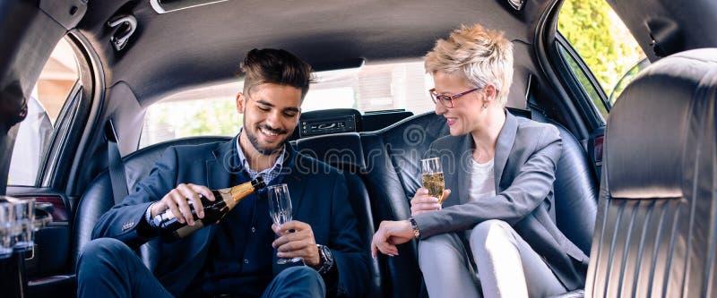 L'homme d'affaires verse le champagne dans la limousine images libres de droits