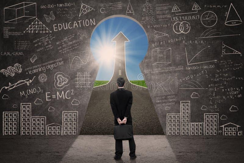 L'homme d'affaires voient le signe de flèche de succès par le trou principal images libres de droits