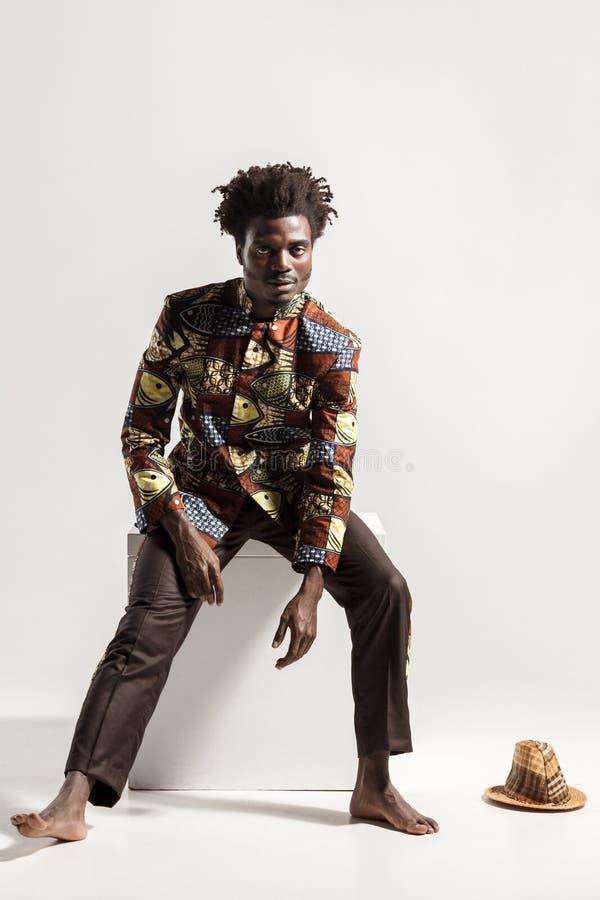 L'homme d'Afro dans le costume national de kongo national s'asseyent sur le coub image stock