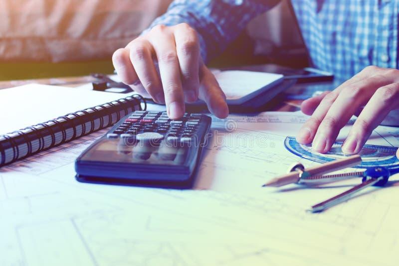 L'homme d'architecte calculent le secteur de construction sur le modèle au bureau photo libre de droits