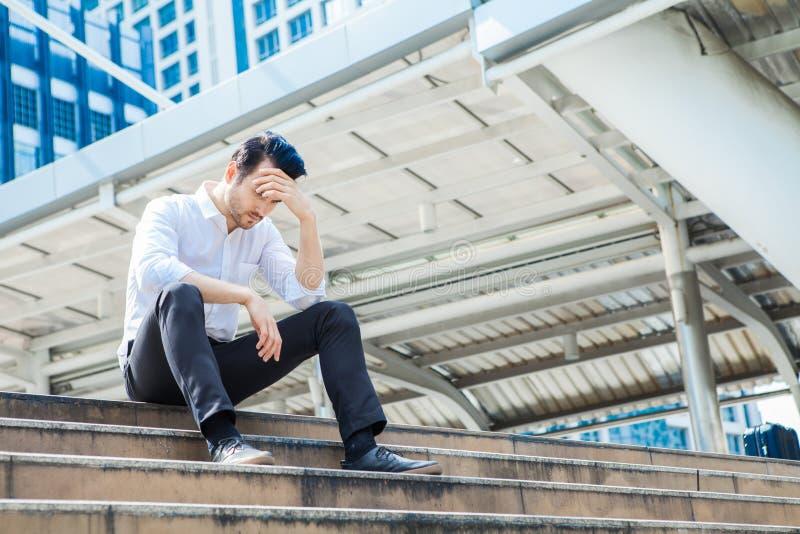 L'homme d'effort seul s'asseyant sur l'escalier extérieur Jeunes affaires images libres de droits