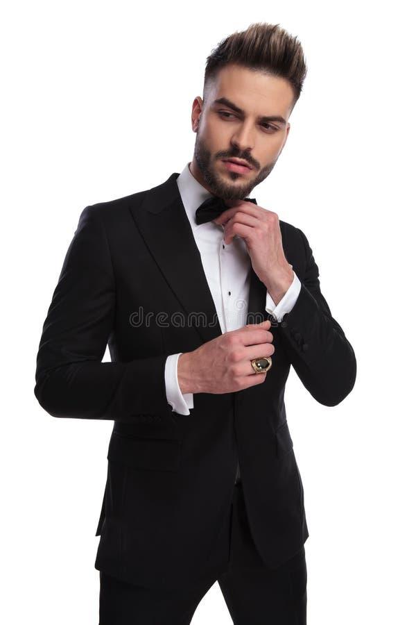 L'homme d'Elegnat dans le smoking fixe son bowtie images stock