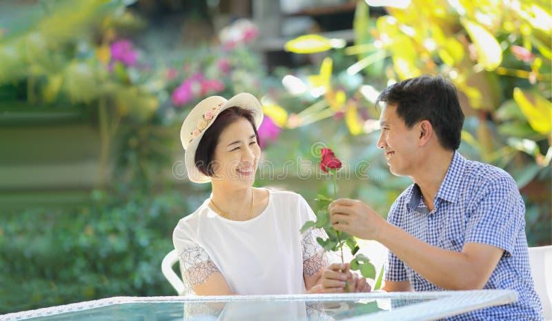 L'homme d'une cinquantaine d'années asiatique donne une rose à son épouse dans le Saint Valentin photographie stock