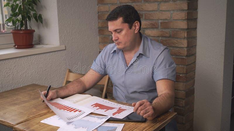L'homme d'une cinquantaine d'années attirant étend des graphiques et des tables sur la table image libre de droits