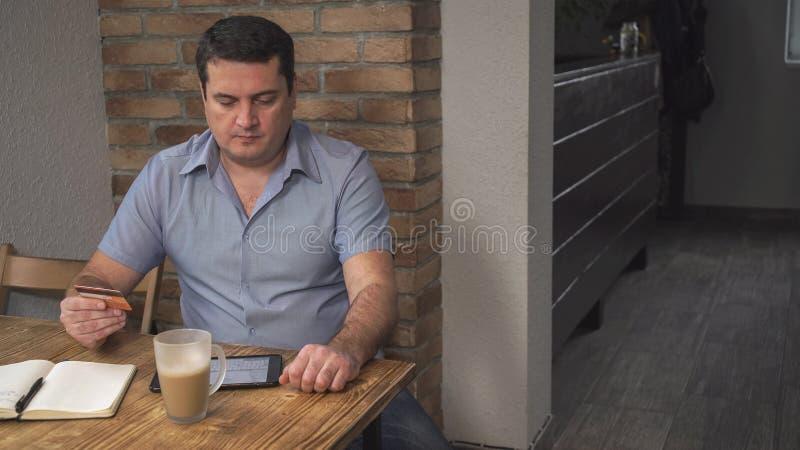 L'homme d'une cinquantaine d'années paye des factures au-dessus de l'Internet dans les mains de la carte de crédit Sur la table e photographie stock