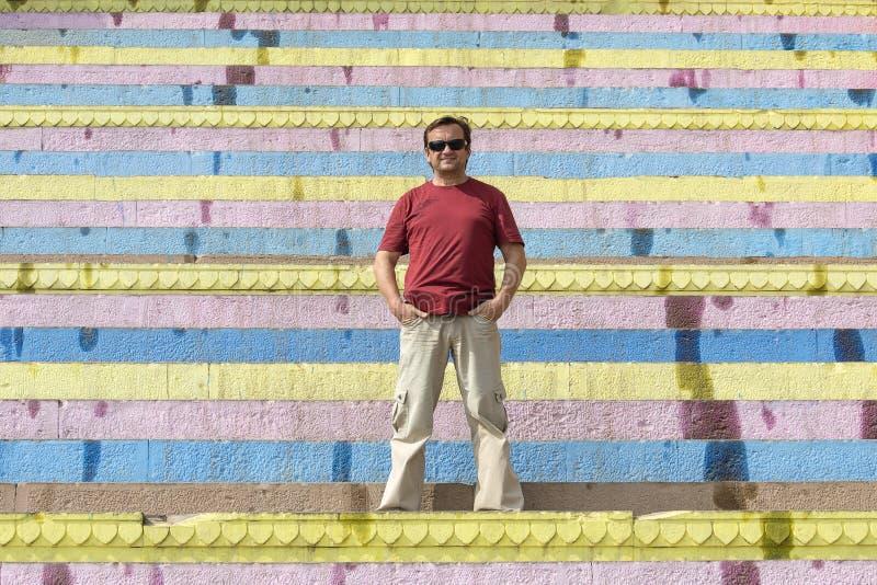 L'homme d'une cinquantaine d'années se tient sur l'escalier coloré dans la ville de Varanasi, Inde photographie stock