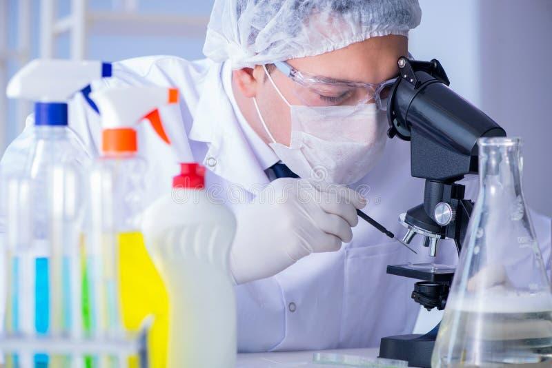 L'homme dans détergent de solution de nettoyage d'essai en laboratoire le nouveau photographie stock