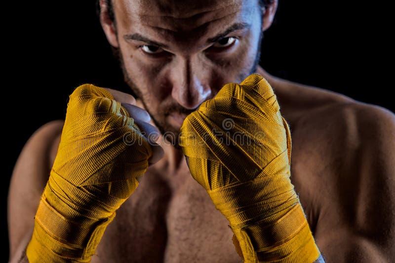 L'homme dans des gants de boxe Jeune combattant de boxeur au-dessus de backgro noir image libre de droits