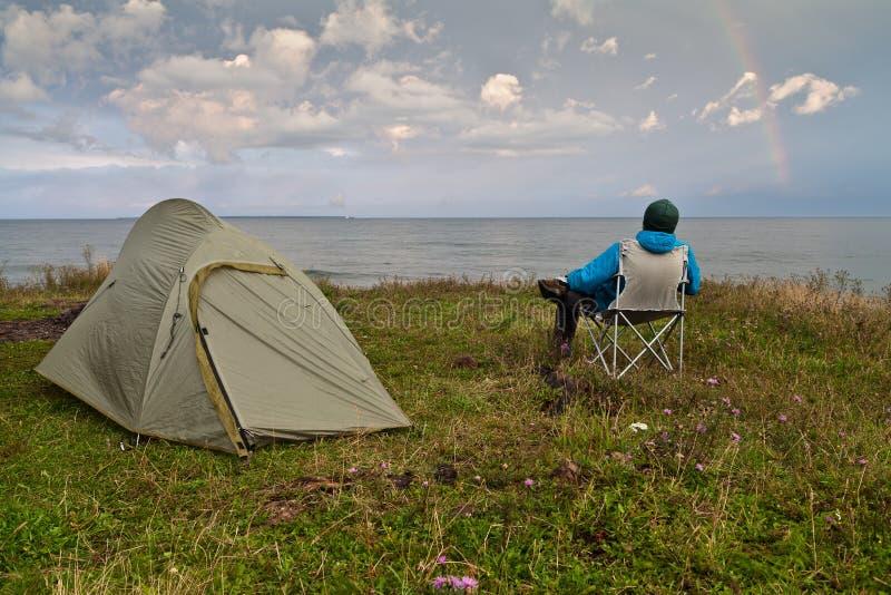 L'homme dans la chaise apprécient la vue scénique du lac Supérieur de son terrain de camping photos libres de droits