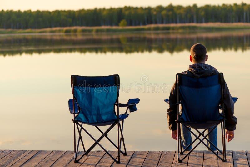 L'homme dans la chaise s'assied près du lac à l'aube et apprécie le beaut image stock