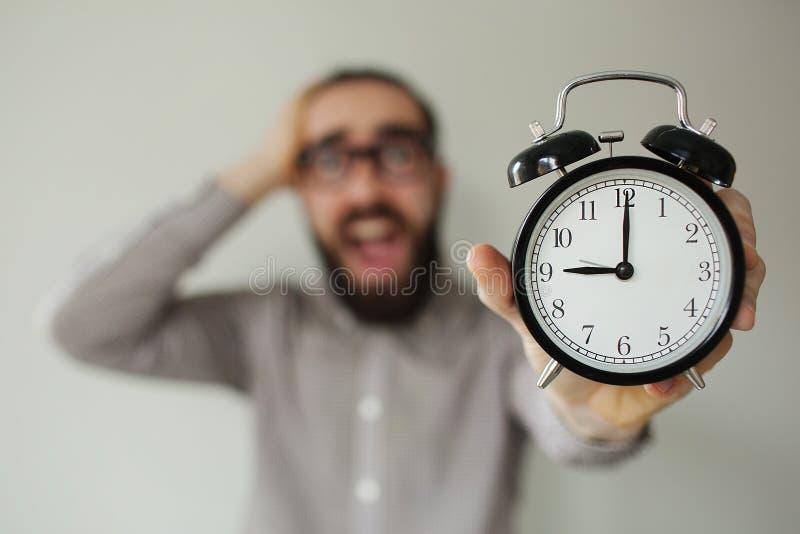L'homme dans la panique tient le réveil et la tête dans la crainte de la date-butoir photo stock