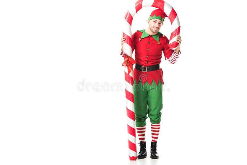 l'homme dans la position de costume d'elfe de Noël sous la grande canne de sucrerie a isolé photographie stock libre de droits
