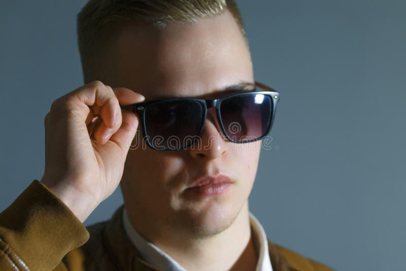 L'homme dans la veste en cuir touche ses lunettes de soleil image stock