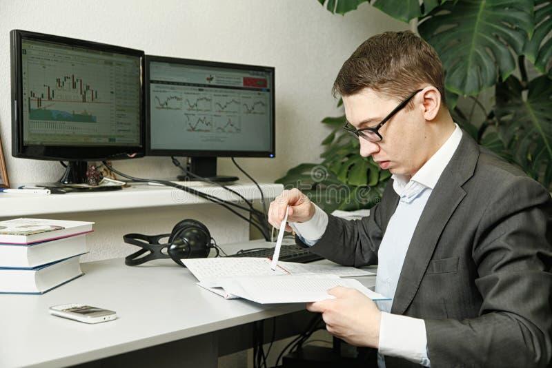 L'homme dans le bureau pour des moniteurs d'ordinateur étudie des disques dans un carnet photographie stock