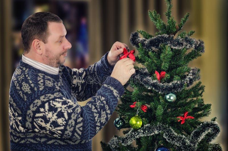 L'homme dans le chandail accroche les arcs rouges sur l'arbre de Noël image libre de droits