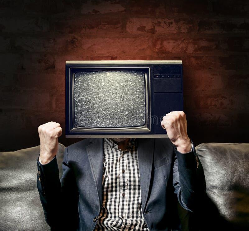 L'homme dans le costume avec le cerveau a lavé la TV images stock
