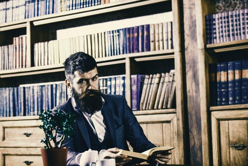 L'homme dans le costume classique s'assied dans l'intérieur de vintage, la bibliothèque, étagères à livres sur le fond Homme démo photographie stock