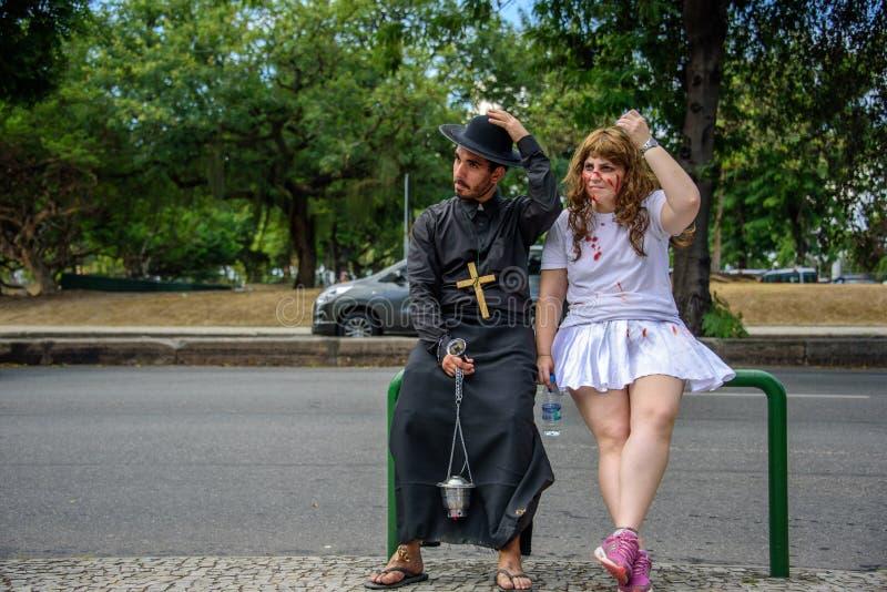 L'homme dans le costume du prêtre et la femme avec le saignement raye sur ses vêtements blancs de port de visage se reposant ense images libres de droits