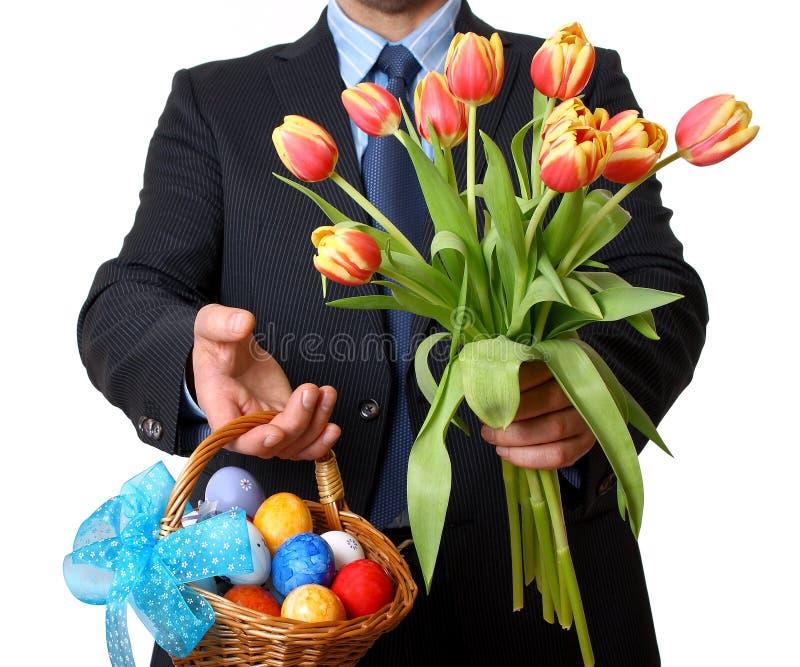 L'homme dans le costume et le lien donne les tulipes et le panier de Pâques image libre de droits